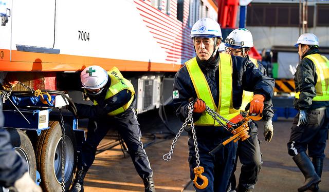 特殊車両の荷台から積み荷の固定具を外し、駅に運び入れた鉄道車両を下ろす。「荷台の下に入るなよ」。安全第一で作業を進める=島根県出雲市、井手さゆり撮影