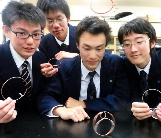 「針金ゴマ」の実験を提案した高校生たち。地上では重い方を上にして回る=茗渓学園高校
