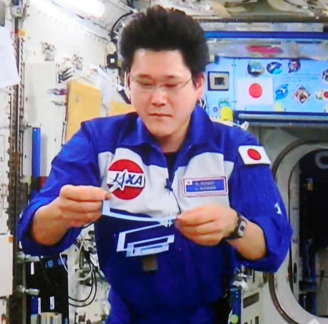 紙で作ったバネをそっと揺らす金井宇宙飛行士=筑波宇宙センターの中継映像