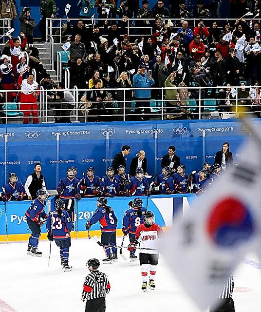 韓国・北朝鮮合同チームが五輪初得点を決め、「統一旗」などを振って喜ぶ観客ら=14日、関東ホッケーセンター、細川卓撮影
