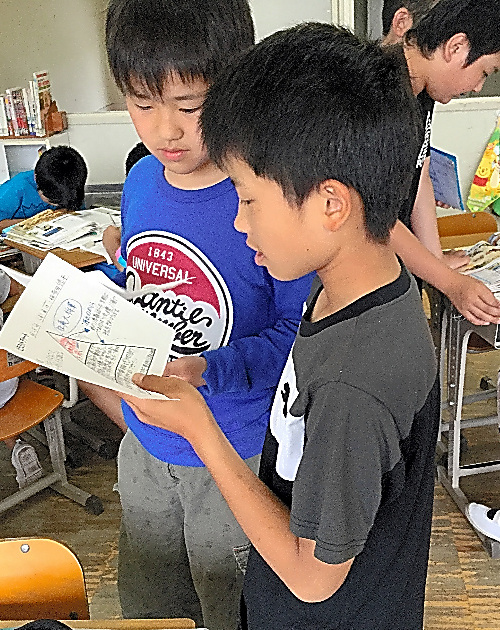 ピラミッドを描いたシートを手に話し合う子どもたち=三重県多気町立勢和小学校、小掠幸太先生提供