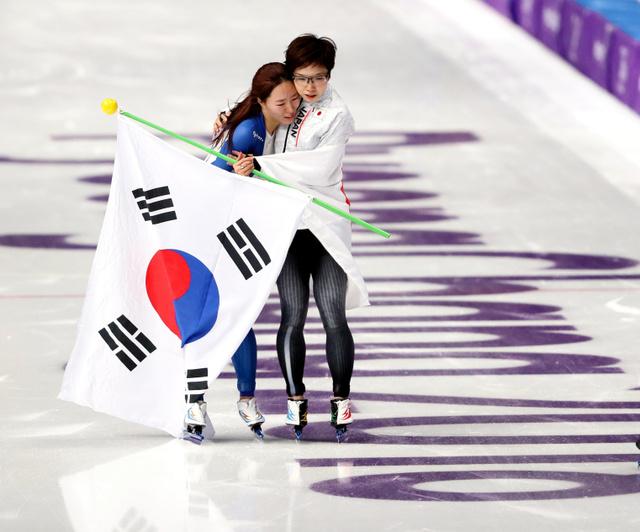 女子500メートルを制した小平奈緒(右)は2位の李相花と抱き合った=18日、江陵オーバル、細川卓撮影