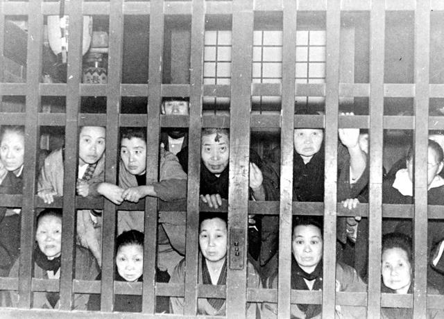 局から格子越しに行法を聴聞する女性たち。昼も夜も、二月堂内は暗いため、聴聞者の姿をこれほどはっきり見ることは難しい=1936年3月撮影