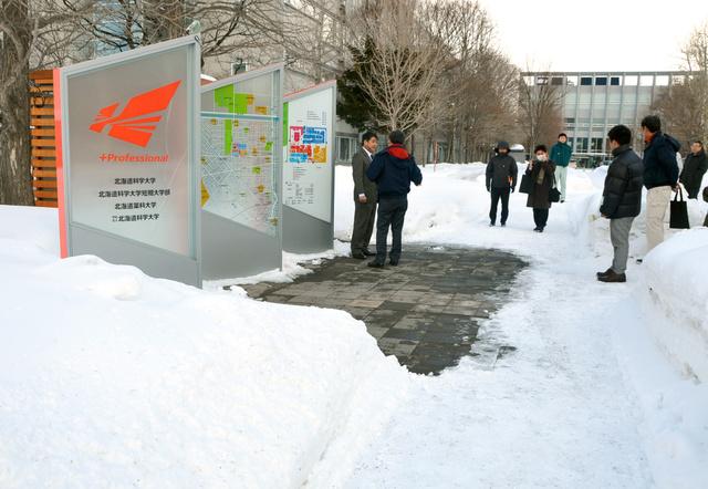北海道科学大正門の案内板付近。下水管の熱で温めるパイプを下に敷設してある路面だけ、雪が解けていた=9日、札幌市手稲区