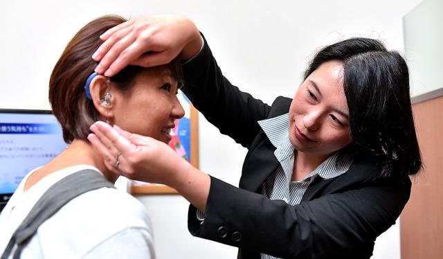 登坂由美恵さん(左)の補聴器の様子をみる細野さん。調整を担当して5年以上になる登坂さんとは、気心の知れた間柄だ=東京都渋谷区、工藤隆太郎撮影