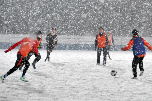 JFLの開幕戦に向けて雪の中で練習するコバルトーレ女川の選手たち。平日の練習開始はたいてい午後6時半。町内の職場から人工芝のホームグラウンドへ集まってくる=2月27日