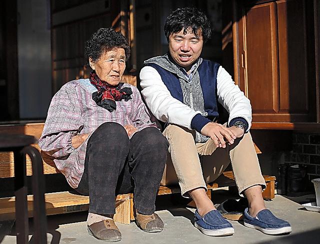 「みんな帰ってこないねえ」。軒先に腰掛けて住民の話を聞く鈴木裕次郎さん(右)=三浦英之撮影