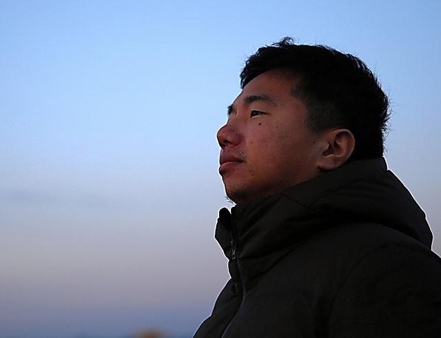 夜明け直後の海を見つめる鈴木裕次郎さん=3月11日午前5時53分、三浦英之撮影