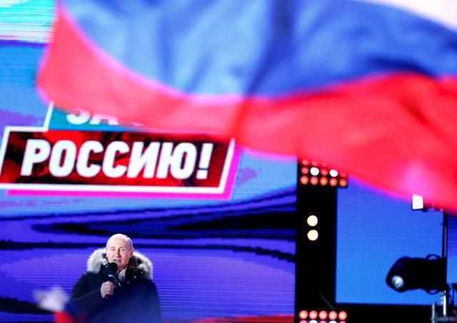 多くの国旗が振られるなか、集会であいさつするロシアのプーチン大統領=18日夜、モスクワ、長島一浩撮影