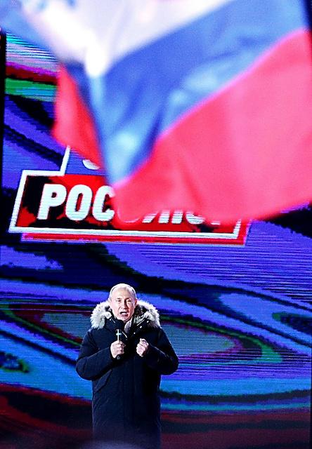 多くの国旗が振られる中、集会で話すプーチン大統領=18日夜、モスクワ、長島一浩撮影