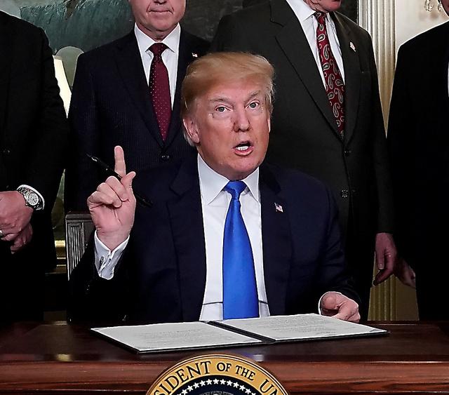 大統領令に署名するトランプ大統領=22日、ロイター