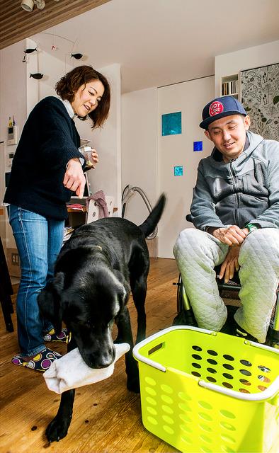 洗濯かごに靴下を入れるようダイキチに指示を出す水上言さん(左)。一度も叱らずに訓練を終えた。「犬がうまく学べないとしたら、人の側に責任があります」=岡山市、横関一浩撮影