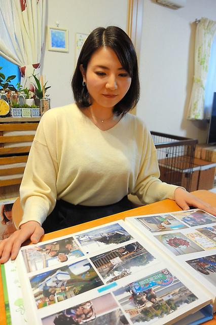 産後うつに苦しんだ当時のアルバムを見る大井さん=3月、大阪府八尾市