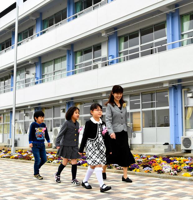 なみえ創成小・中学校校舎の落成式を終え、校舎に戻る新1年生の児童3人=2018年4月6日午前、福島県浪江町、福留庸友撮影
