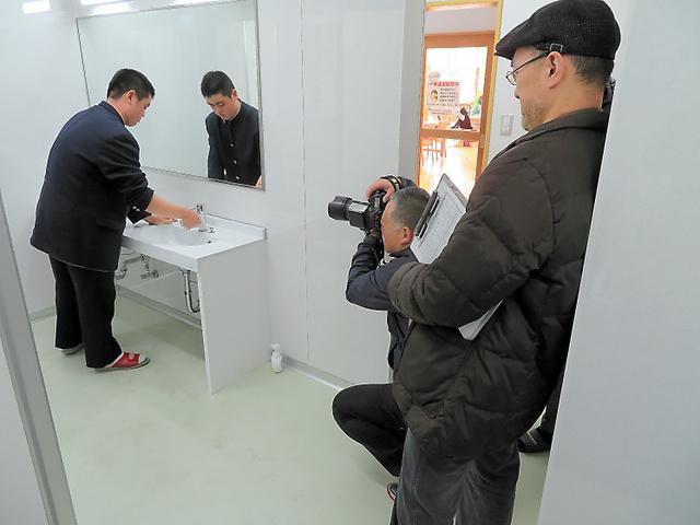 あさぎり中学校のトイレの掃除風景を撮影する取材スタッフ=熊本県あさぎり町