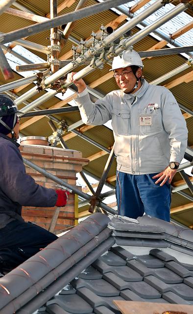 修復を進めている「長崎居留地二十五番館」の屋根上で、職人と言葉を交わす石川新太郎さん(右)=愛知県犬山市の博物館明治村、小川智撮影