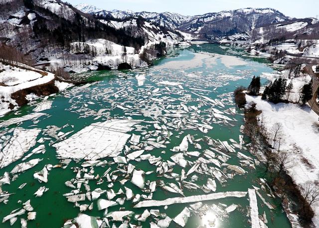 ダム湖の水面を漂う雪の塊=2018年4月10日午後、新潟県魚沼市、長島一浩撮影