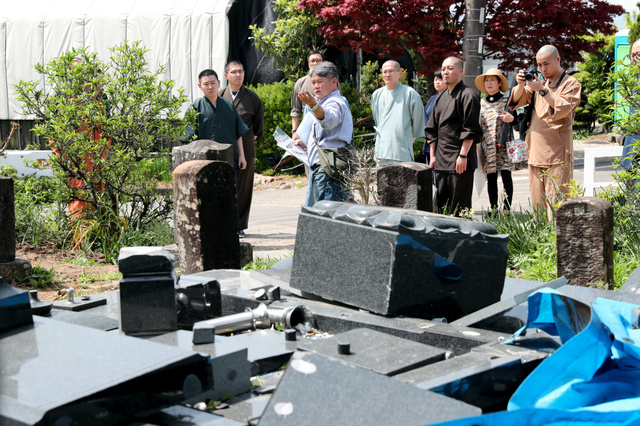 スタディーツアーで壊れた墓石の前で地震の影響などを説明する田崎真一さん(中央)=12日午後1時2分、熊本県益城町東無田、小宮路勝撮影