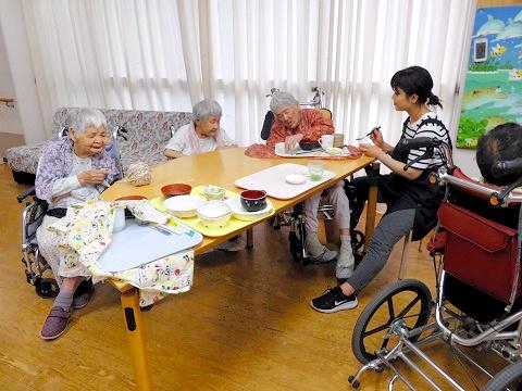 夕食の時間。刻み食など一人ひとりに合った食事が用意される。最高齢の佐古美也子さん(中央)は眠ることもあり、支援員が言葉をかけ介助する=2017年6月14日、群馬県高崎市の国立のぞみの園「なでしこ寮」