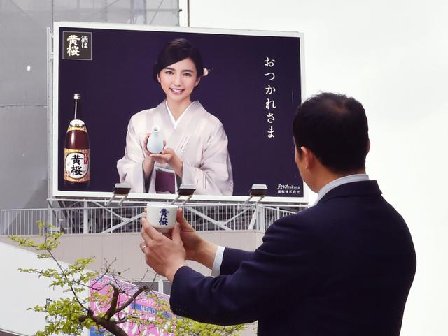 「おつかれさま」。新大阪に帰ってきた乗客らを癒やしてくれる、黄桜の看板。「お酌」してもらっているのは、黄桜の久保田淳さ…