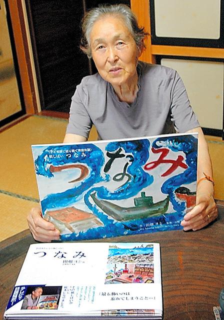 絵本になった紙芝居を手にする田畑ヨシさん=2011年8月、岩手県宮古市田老の妹宅