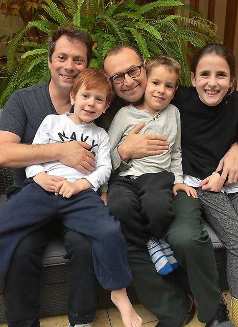 代理出産で3人の子をもうけたゲイカップルのタッツァさん(左)とラオールさん(中央)=テルアビブ近郊、渡辺丘撮影