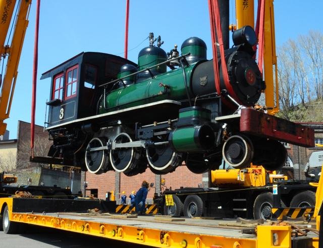 2台のクレーンでつり上げ、トレーラーに載せられるアイアンホース号=小樽市