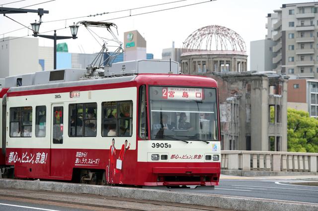 京急カラーにラッピングされた広電の車両。右奥は原爆ドーム=23日午後、広島市中区、上田幸一撮影