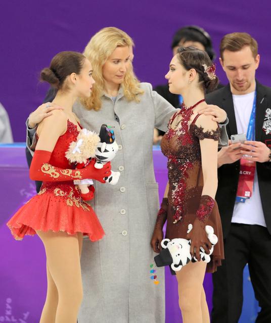 平昌五輪女子シングルのセレモニーで、トゥトベリゼコーチ(中央)から祝福される銀メダルのメドベージェワ(右)と金メダルのザギトワ