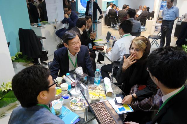 イランの首都テヘランで行われた産業展示会の日本企業ブースで、商談を交わすイラン人ら=2016年5月7日、神田大介撮影