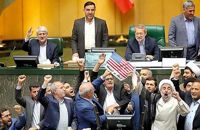 テヘランのイラン国会で9日、米国を非難するスローガンを唱えながら、米国旗を模した紙に火をつけて燃やすイランの国会議員=AP