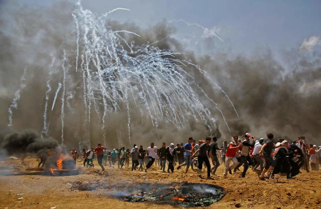 パレスチナ自治区ガザ地区で14日、米大使館のエルサレム移転に反対するデモでイスラエル軍が放った催涙弾から逃げるパレスチナの人々=AFP時事