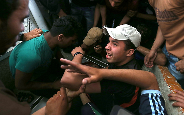 ガザ地区の病院にはデモで亡くなった男性が仲間たちに付き添われて、運び込まれた=14日午後、パレスチナ自治区ガザ地区、杉本康弘撮影