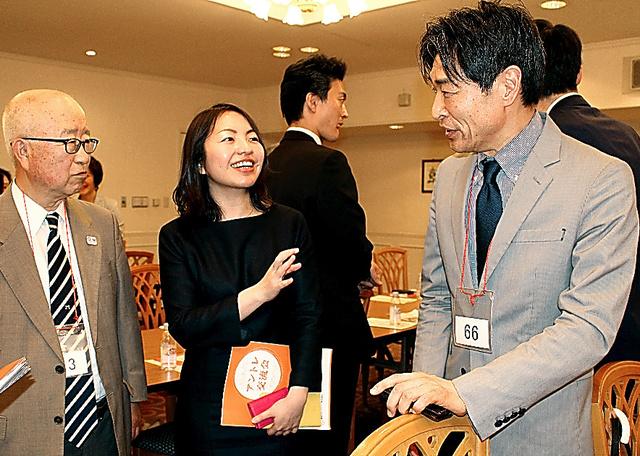 シニア起業家の交流会で上村耐治(右)と談笑する片桐実央(中央)。月に1度開かれ、毎回70~100人が参加する=4月24日、東京都中央区