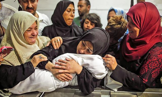 ガザ地区の病院で15日、抗議デモ中に催涙ガスを吸って亡くなったという生後8カ月のライラちゃんの遺体を抱きしめる母親(中央)=AFP時事