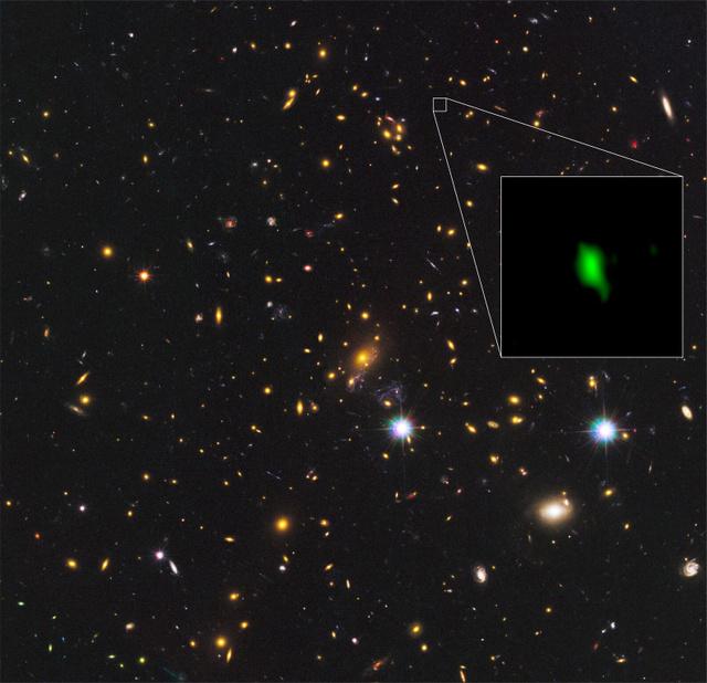 アルマ望遠鏡が観測した132・8億光年かなたにある銀河の画像(拡大部分)。緑色は酸素の分布を表す。ハッブル宇宙望遠鏡が撮影した周辺画像と合成した(国立天文台提供)