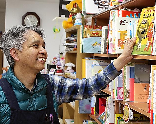 約1千冊の品ぞろえが自慢の絵本を手に取る後中淳司=兵庫県西宮市