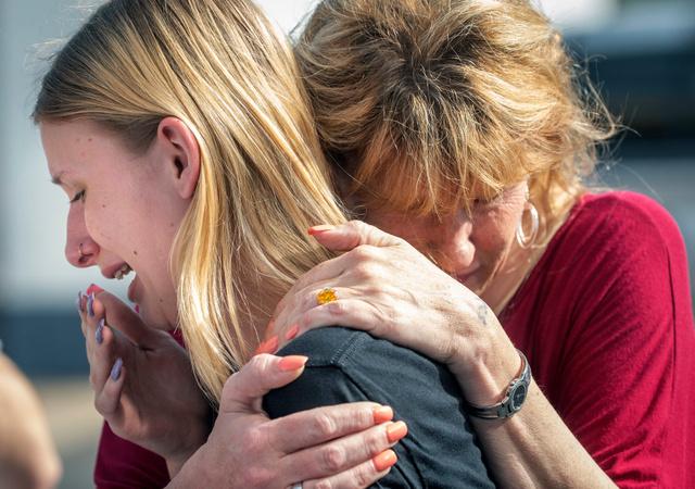 米テキサス州のサンタフェ高校で18日、銃撃事件後に母親に慰められる同校の生徒。友人が撃たれたという。地元紙ガルベストン・カントリー・デイリー・ニュース提供=AP