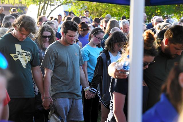 追悼集会で手を取り合って犠牲者に祈りを捧げる高校生ら=18日、米テキサス州サンタフェ、金成隆一撮影
