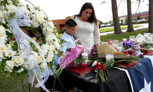 米テキサス州サンタフェで19日、高校での銃撃事件の犠牲者の追悼のために花を捧げる母子=AP