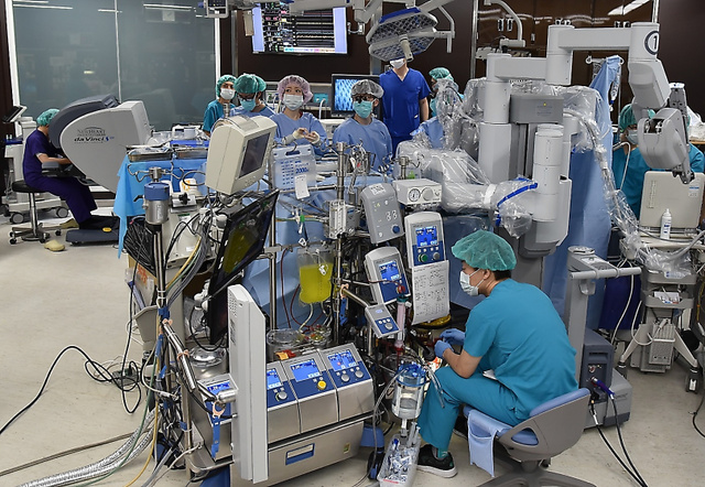ダビンチを使って心臓の弁形成術をするスタッフたち。渡辺剛医師(左端)が手術台から離れた場所で機械を操作する=東京都のニューハート・ワタナベ国際病院