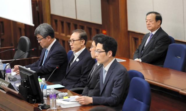 23日、ソウル中央地裁で開かれた初公判で被告席に座る李明博元大統領(左から2人目)=東亜日報提供