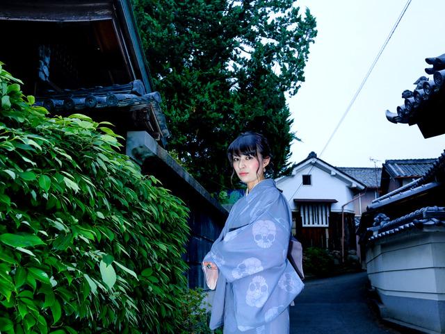 「砂かけ」の妖怪が出たという寺の前の道。妖怪文化研究家の木下昌美さんに、異界の者らしくポーズを取っていただいた=奈良県河合町、槌谷綾二撮影