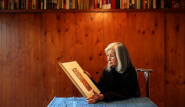 映画「乱」でデザインした衣装を施した額を手にする衣装デザイナーのワダエミさん=東京・世田谷、飯塚悟撮影