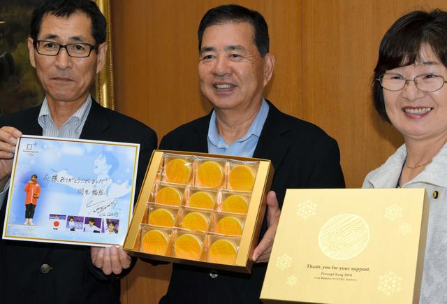 金メダルチョコを手にする河田晃明市長(中央)=2018年6月12日、埼玉県羽生市役所