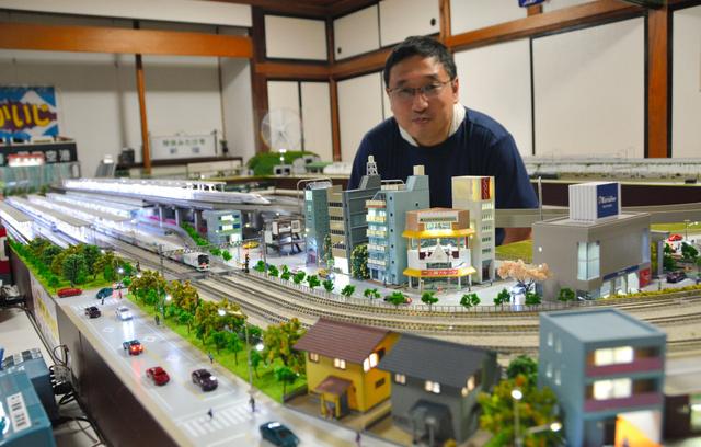オーナーの山田裕輝さんと自慢の鉄道模型のジオラマ=2018年5月12日、山梨県笛吹市春日居町鎮目