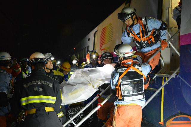 担架とはしごを使って「けが人」を搬送する救助隊員=2018年6月15日午前3時13分、群馬県高崎市八島町