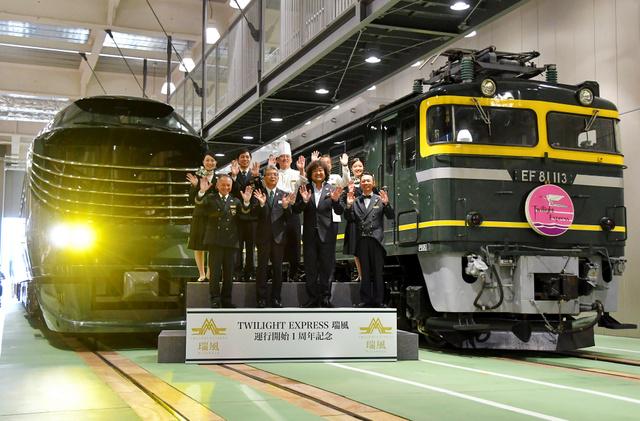 新旧のトワイライトエクスプレスが並ぶ中、乗務員らが記念撮影に応じた=京都市下京区の京都鉄道博物館
