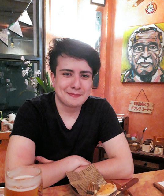 コロンビア人留学生のオマル・エレラさん(22)。壁には母国のノーベル文学賞作家ガルシア・マルケスの絵が飾られていた=大阪市浪速区