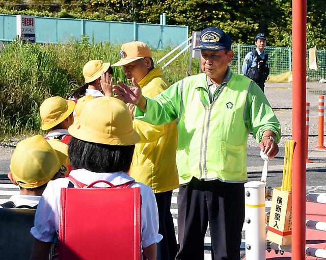 ハイタッチをしながら小学生の登校を見守る小垣江向友愛クラブのメンバーら=刈谷市